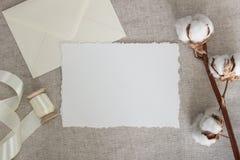 在亚麻布的被撕毁的边缘纸牌与棉花花和丝绸丝带 婚礼文具大模型 书法模板 库存照片