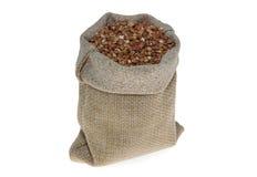 在亚麻制袋子的荞麦在白色 图库摄影