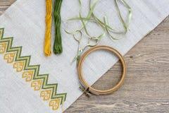 在亚麻制织品和螺纹刺绣的乌克兰刺绣在一张木桌上 免版税图库摄影