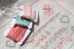 在亚麻布和螺纹三个片盘的十字绣刺绣  免版税库存照片