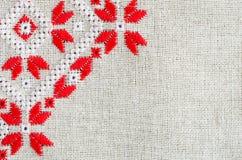 在亚麻布的元素手工制造刺绣由红色和白色棉花螺纹 与刺绣的背景 免版税库存图片