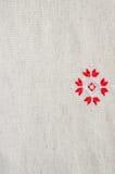 在亚麻布的元素手工制造刺绣由红色和白色棉花螺纹 与刺绣的背景 图库摄影