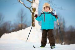 在交叉的愉快的小男孩滑雪 免版税库存照片