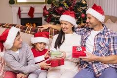 在交换礼物的圣诞老人帽子的欢乐的家庭 图库摄影
