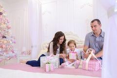 在交换礼物的欢乐心情的友好的家庭坐床 免版税库存图片