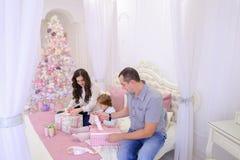 在交换礼物的欢乐心情的友好的家庭坐床 图库摄影