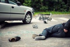 在交通事件以后的死的受害者与在路的一辆残破的汽车 库存照片