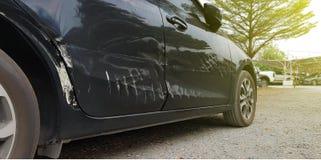 在交通事故以后的一辆被砸的汽车,黑汽车后面从在路的事故得到损坏 汽车打破的车丰收凹痕 库存图片