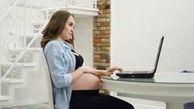 在产假期间,一名孕妇参与事务 坐在抚摸她的腹部和谈话的计算机 股票录像