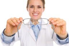 在产生眼睛玻璃的医生妇女的特写镜头 库存照片
