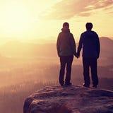 在享受嫩片刻的爱的夫妇在日落期间 年轻对远足者在岩石帝国峰顶手拉手停放 免版税库存照片
