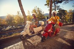 在享受旅途的滑行车的愉快的夫妇在度假在日落 库存图片