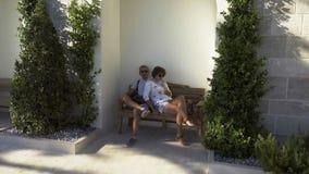 在享受日落的长凳的一更旧的夫妇选址 股票录像