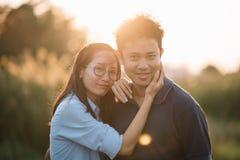 在享受日落的阳光火光的年轻亚洲夫妇放松获得乐趣 免版税库存照片