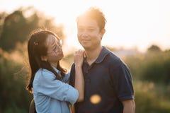 在享受日落的阳光火光的年轻亚洲夫妇放松获得乐趣 库存照片