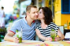 在享受时间的咖啡馆的年轻夫妇在假日 图库摄影