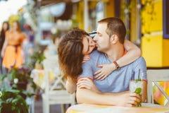 在享受时间的咖啡馆的年轻夫妇在假日 免版税图库摄影