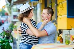 在享受时间的咖啡馆的年轻夫妇在假日 免版税库存图片
