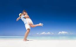 在享受晴天的明亮的衣裳的浪漫夫妇在热带海滩 免版税库存照片