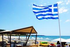 在享受他们的假期的海滩和游人的希腊旗子 免版税图库摄影