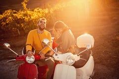 在享用在浪漫的滑行车的愉快的夫妇在旅途上在日落 库存照片