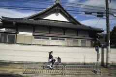 在京都日本街道上的自行车女孩 图库摄影