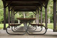 在亭子下的空的野餐桌 库存照片