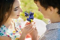 在亲吻和拥抱在蓝色花的爱的年轻夫妇 关闭 免版税库存照片