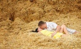 在亲吻的一对夫妇在干草 图库摄影