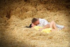 在亲吻的一对夫妇在干草 免版税库存图片
