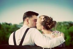 在亲吻在一条长凳的爱的年轻夫妇在公园 葡萄酒 图库摄影