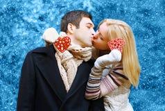 在亲吻在冬天的爱的愉快的相当年轻夫妇 免版税库存照片