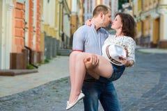 在亲吻在城市的爱的愉快的夫妇 免版税库存图片
