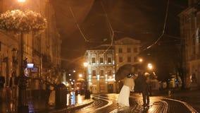 在亲吻在夜城市街道上的雨下的减速火箭的穿戴的夫妇,掩藏从雨在伞下 影视素材