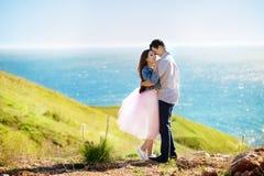 在亲吻在日落的爱的夫妇-恋人在一个浪漫日期户外 愉快的生活方式概念 免版税库存图片