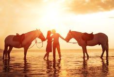 在亲吻在海滩的爱夫妇 在日落, summe的两匹马 免版税库存照片