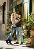 在亲吻在街道上的爱的年轻美好的夫妇庆祝与玫瑰色礼物的情人节 免版税库存图片