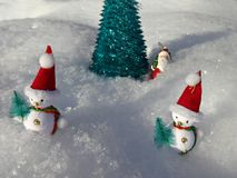 在人为圣诞树附近的雪人在雪 免版税库存图片