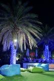 在人为草的放松沙发与美丽的棕榈 免版税图库摄影