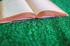 在人为草的老被打开的书 免版税库存图片