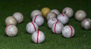 在人为草的老高尔夫球 免版税库存图片