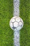 在人为草皮橄榄球场绿色白色栅格的老橄榄球 库存图片