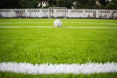 在人为草皮橄榄球场绿色的老橄榄球 库存图片