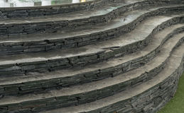 在人为草皮的石头和曲线楼梯 免版税库存照片