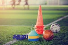 在人为草皮的红色橄榄球和足球训练器材 库存图片