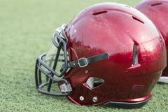 在人为草皮的红色橄榄球盔 免版税库存照片
