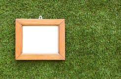 在人为草背景的木制框架 库存图片