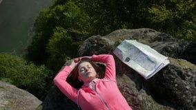 在人和自然之间的和谐 说谎在与指南针,地图的岩石的年轻旅游妇女 免版税图库摄影