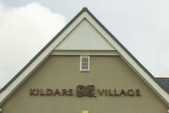 在人字墙上的一个大标志在对有名望的基尔代尔村庄零售公园的入口在基尔代尔郡爱尔兰 免版税库存图片