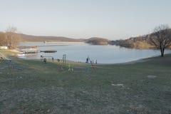 在人工湖前面的海滩秋天天气的 免版税库存图片